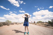 USA, Utah, Arches National Park, woman with straw hat standing on dirt track to the Windows Section — Stock Photo