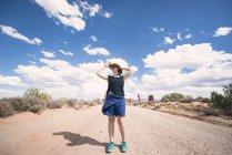 EUA, Utah, Arches National Park, mulher com chapéu de palha em pé na pista de terra para a seção do Windows — Fotografia de Stock