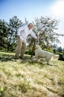Senior man playing with dog on a meadow — Stock Photo