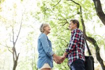 Happy cute senior couple holding hands at park — Stock Photo