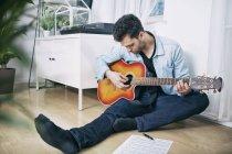 Joven sentado en el suelo tocando la guitarra - foto de stock