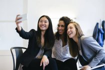 Three businesswomen taking selfies with a smart phone — Stock Photo