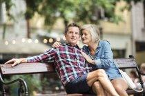 Felice coppia anziana che si abbraccia sulla panchina al parco — Foto stock