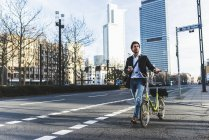 Німеччина, Франкфурт, Молодий підприємець в місті з велосипеда, за допомогою мобільного телефону — стокове фото