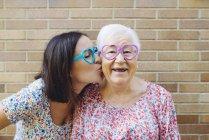 Счастливая внучка и бабушка в очках в форме сердца — стоковое фото