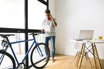 Teenage boy on the phone standing in apartment with bicycle — Stock Photo