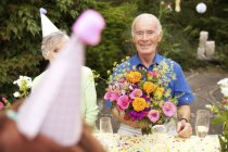Seniors celebrating birthday party in garden — Stock Photo