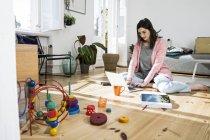 Красива кавказька брюнетка жінка, сидячи на підлозі поруч іграшки і працюють на ноутбук — стокове фото