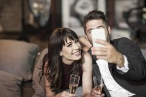 Smiling couple in elegant clothing drinking champagne in bed and taking a selfie — Stock Photo