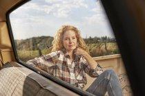Confiante femme assise en van dans la nature — Photo de stock