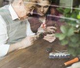 Senior homme et petit-fils réparation jouet s'entraînent à la maison — Photo de stock