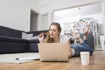 Giovane donna a casa che si trova sul pavimento per mezzo del computer portatile — Foto stock