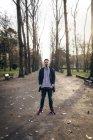 Jeune homme debout dans le parc avec les mains dans ses poches — Photo de stock