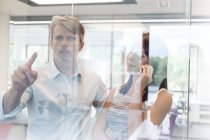 Business people in office touching glass screen — Stock Photo