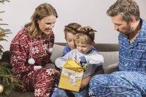 Родители смотрят, как мальчик разворачивает рождественский подарок — стоковое фото