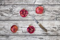 Whole and halved organic pomegranates — Stock Photo