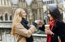 Two friends exploring the city, drinking coffee in front of Southwark Cathedral, London, UK — Stock Photo