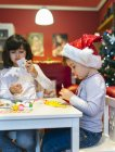 Portrait of two little girls tinkering Christmas decoration — Stock Photo