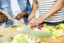 Cropped view of people preparing salad on chopping board — Stock Photo
