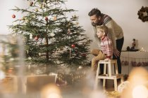 Father and son decorating Christmas tree at home — Stock Photo