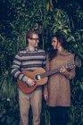 Sorridente giovane uomo che suona la chitarra guardando la donna — Foto stock