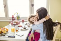 Girl hugging mother at breakfast table — Stock Photo