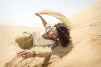 Man rolling down sand dune — Stock Photo