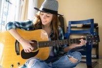 Sonriente a mujer joven tocando guitarra en el interior - foto de stock