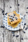 Stack of waffles with icing sugar and blueberries on plate — Stock Photo