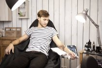 Client watching his new tattoo in a tattoo studio — Stock Photo