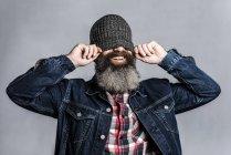 Homme barbu mettant chapeau laineux et couvrant ses yeux — Photo de stock