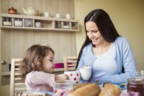 Mother and little daughter toasting with cups — Stock Photo