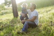 Отец играет со своей маленькой дочерью на лугу — стоковое фото