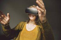 Femme portant des lunettes de réalité virtuelle à l'aide de ses mains — Photo de stock