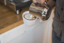 Close-up of male hand pouring milk froth in cup of cappuccino — Stock Photo
