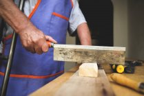 Man with crutch sawing piece of wood on workbench — Stock Photo