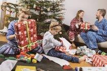 Garçons déballer un cadeaux de Noël et les parents assis sur le canapé sur le fond — Photo de stock