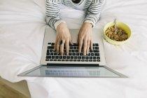 Mujer con portátil y tazón de muesli - foto de stock