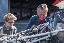 Nonno e nipote riparare biplano — Foto stock