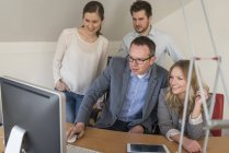 Four colleagues in office looking at computer monitor — Stock Photo