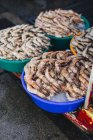 Shrimps in colored bowls  on a market — Stock Photo