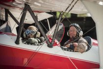 Grandfather and grandson sitting on old biplane — Stock Photo