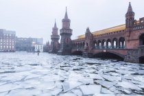 Germany, Berlin, Oberbaum Bridge with driving underground train in winter — Stock Photo