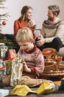 Little boy happily looking at Christmas gift with parents on background — Stock Photo