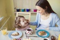 Madre e figlioletta a tavola a colazione — Foto stock