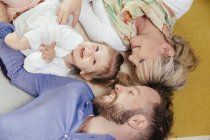 Family of three lying down on carpet at home — Stock Photo
