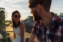 Retrato de Austria, Viena, de joven sonriente con gafas de sol de ligar en una terraza en la azotea - foto de stock