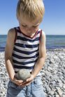 Portrait of a blond boy carrying stone on beach — Stock Photo