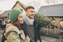 Happy couple with a tree walking over the Christmas Market — Stock Photo