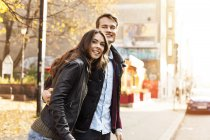 Germany, Berlin, happy couple at the roadside looking around — Stock Photo